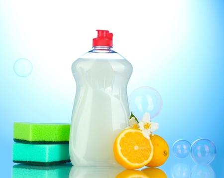 Dishwashing liquid with sponges and lemon with flowers on blue background Stock Photo - 14181922