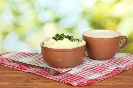 Mashed potato in the bowl and cup with milk on colorful napkin on wooden background photo