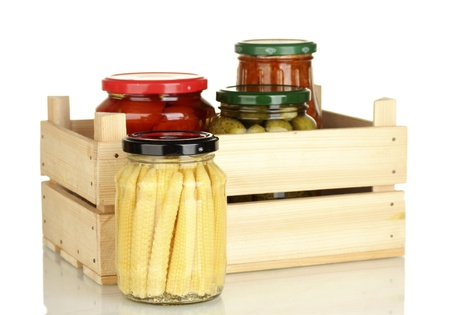 Jars with canned vegetables in wooden box isolated on white photo