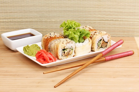 Tasty rolls served on white plate with chopsticks on wooden table on light background Stock Photo - 14226011