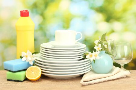 empty clean plates, glasses and cups with dishwashing liquid, sponges and lemon on wooden table on green background photo