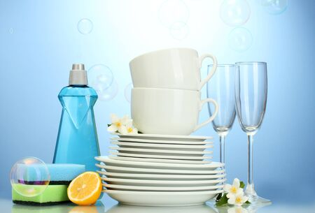 clean dishes: empty clean plates, glasses and cups with dishwashing liquid, sponges and lemon on blue background