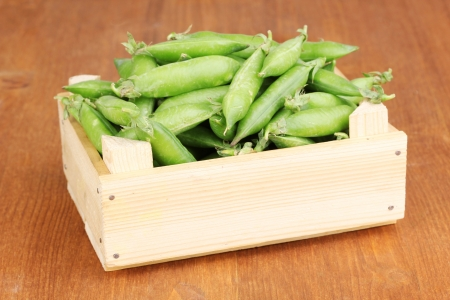 Green peas in crate on wooden background photo