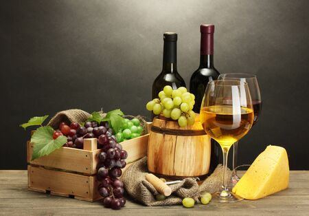 barrel, bottles and glasses of wine, cheese and ripe grapes on wooden table on grey background photo