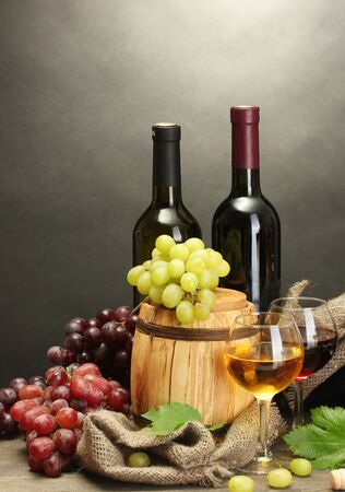 barrel, bottles and glasses of wine and ripe grapes on wooden table on grey background Stock Photo - 14225985