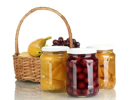 frutta sciroppata: Vasetti di conserve di frutta e cesto con frutta isolato su bianco