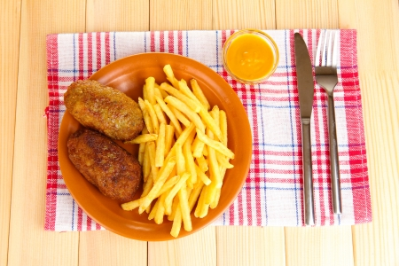 Potatoes fries with burgers on the plate on wooden background close-up photo