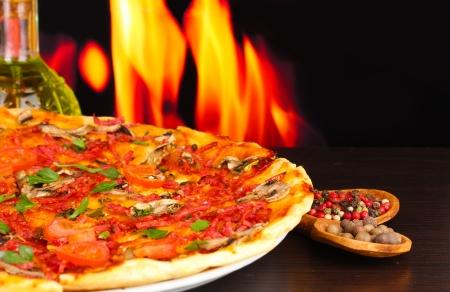 masa: deliciosa pizza con verduras y embutidos en la mesa de madera en el fondo de la llama Foto de archivo