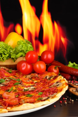 delicious pizza, salami, vegetables and spices on wooden table on flame background photo