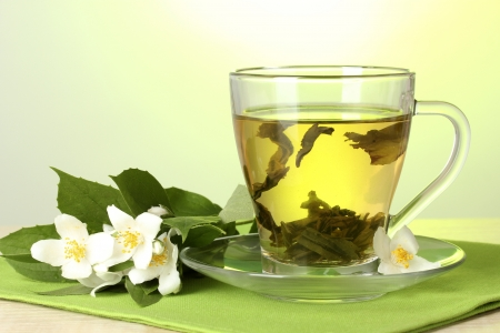 cup of green tea with jasmine flowers on wooden table on green background photo