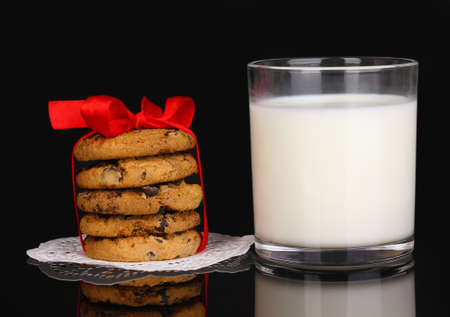Glass of milk and cookies isolated on black photo