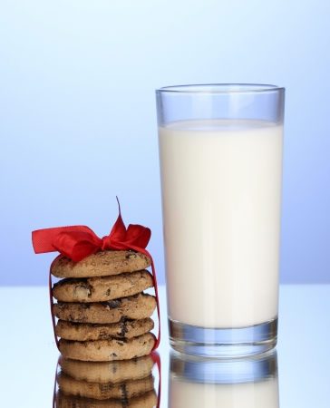 Glass of milk and cookies on blue background Stock Photo - 14292446
