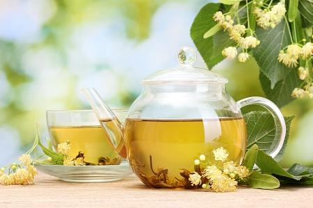 teepflanze: Teekanne und Tasse mit Linden Tee und Blumen auf Holztisch im Garten