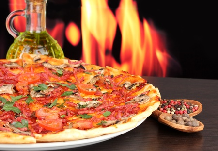 delicious pizza with vegetables and salami on wooden table on flame background photo