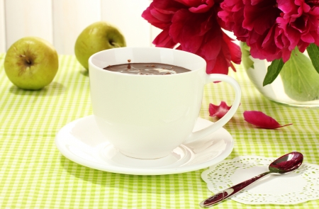 cup hot chocolate, apples and flowers on table in cafe photo