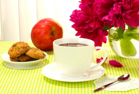 cup hot chocolate, apple, cookies and flowers on table in cafe photo