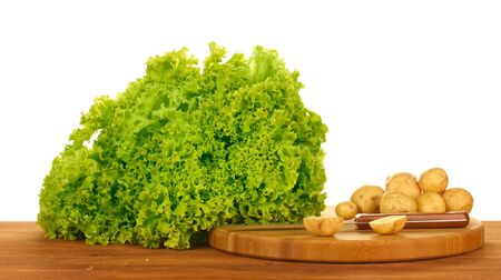 young potatoes and lettuce on a cutting board with knife on a table on white background close-up Stock Photo - 14352674
