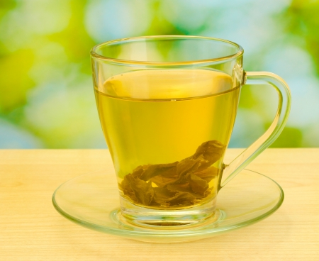 green tea in cup on wooden table in garden photo