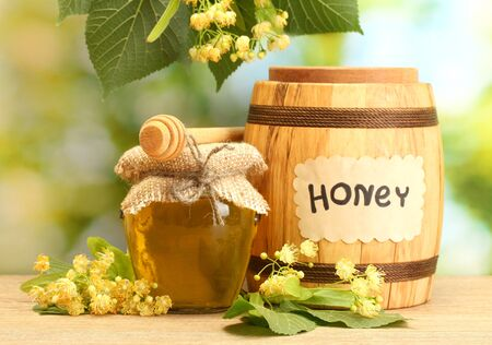jar and barrel with linden honey and flowers on wooden table on green background photo
