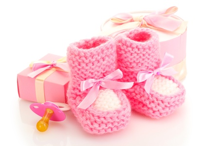 pink baby boots, pacifier, gifts and flower isolated on white photo