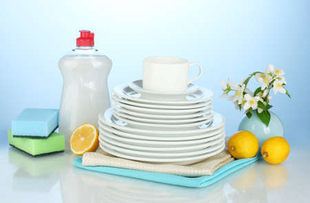 empty clean plates and cups with dishwashing liquid, sponges and lemon on blue background photo