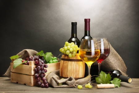 barrel, bottles and glasses of wine and ripe grapes on wooden table on grey background Stock Photo - 14354499