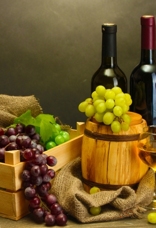 barrel, bottles and glasses of wine and ripe grapes on wooden table on grey background photo