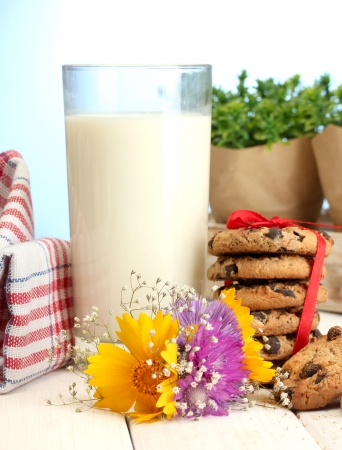 glass of milk, chocolate chips cookies with red ribbon and wildflowers on wooden table on blue background photo
