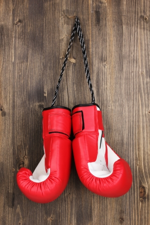 arts backgrounds: Red boxing gloves hanging on wooden background