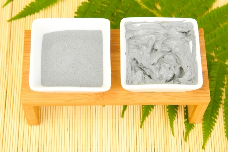 cosmetic clay for spa treatments on straw background close-up photo