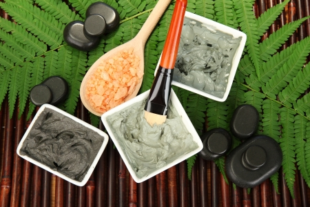 aroma facial: cosmetic clay for spa treatments on bamboo background close-up