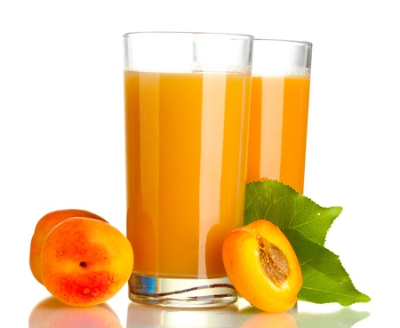 two glasses of apricot juice and apricots with leaves isolated on white photo