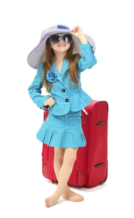 Portrait of little girl with travel case, sunglasses and hat isolated on white photo