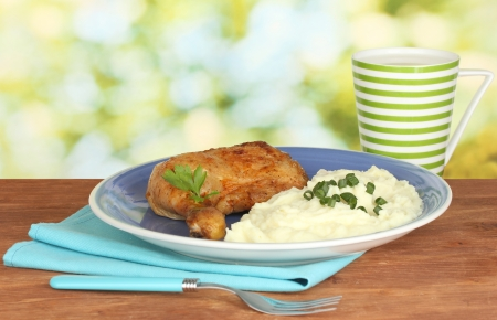 roasted chicken leg with mashed potato in the plate and cup with milk on wooden table on bright background close-up photo