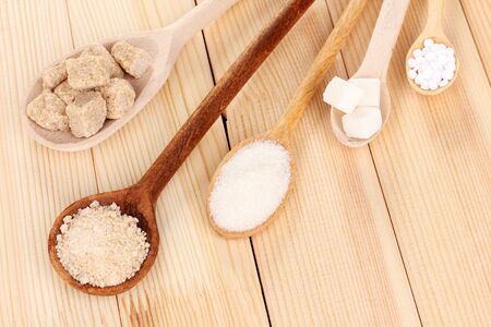 Sweetener with white and brown sugar in spoons on wooden background photo