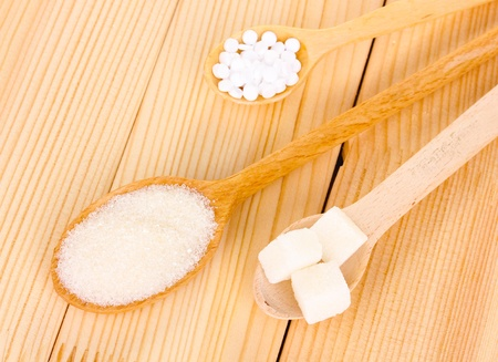 Sweetener and white sugar in spoons on wooden background photo