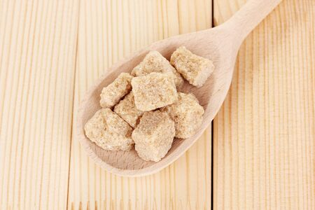 Brown sugar in spoon on wooden background photo