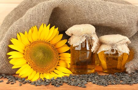sunflowerseed: sunflower oil and sunflower on wood background Stock Photo