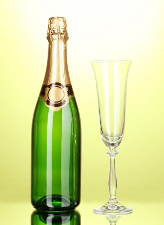 gold capped: Bottle of champagne and goblet on green background