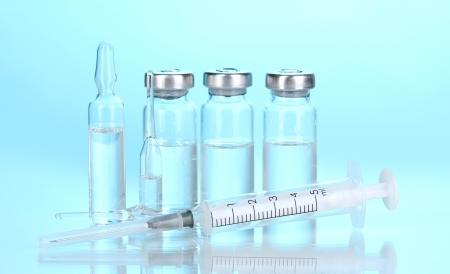 Syringe and medical ampoules on blue background photo