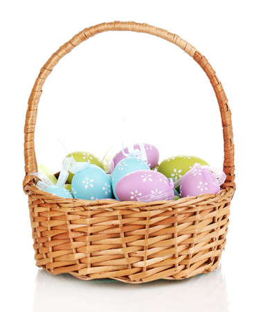 Colorful easter eggs in basket isolated on white photo