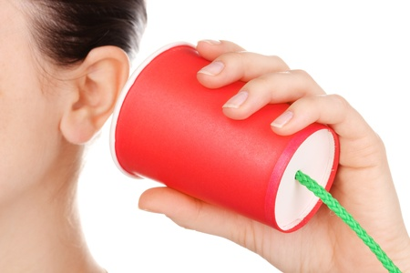 perceptie: Menselijk oor en kartonnen beker in de buurt van het close-up op wit wordt geïsoleerd