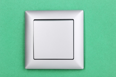 Modern light switch on green background photo