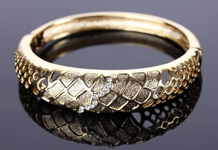 Beautiful golden bracelet with precious stones on grey background photo