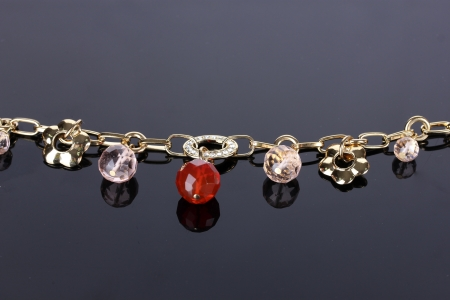 Beautiful golden bracelet with precious stones on grey background photo