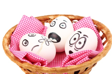 White eggs with funny faces in basket isolated on white photo