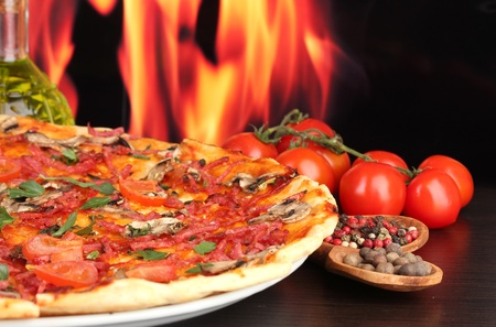 delicious pizza and tomatoes on wooden table on flame background photo