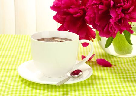 cup hot chocolate and flowers on table in cafe photo
