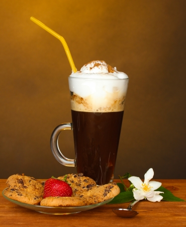 glass of coffee cocktail with cookies and strawberry on saucer and flower on brown background photo