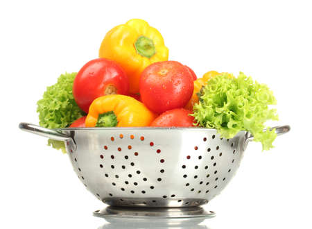 fresh vegetables in silver colander isolated on white photo